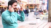 escuta : Man with headphones listening music and having fun in the city. Middle eastern man alone sitting at a table and relaxing. Lifestyle and relax concepts