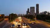 estados : Chicago highway and skyline at dusk. Chicago downtown with illuminated skyscrapers at night on background, blurred cars on the road in foreground. Pan movement. Travel and architecture concepts.