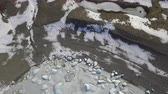 seyahat : Aerial view of icebergs and frozen ground in Iceland. Above view of a glacier lagoon with ice pieces and snow on the side. Travel and winter concepts Stok Video