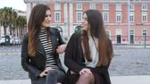 Португалия : Two women talking in Lisbon. Two beautiful girls spending time together on a winter day, talking and having fun. Friendship and lifestyle concepts Стоковые видеозаписи