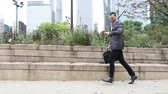 captura : Business man running in Chicago downtown, looking at his watch, being late and trying to catch up. Slow motion side video of a businessman during rush hour