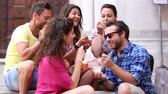 cream : Tourists or friends eating ice cream slush, talking and looking each other. Five persons having fun together on a hot summer day in Pisa, Italy. Women and men sitting on concrete steps and relaxing. Stock Footage