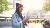 kurtka : Black young woman typing on smart phone in Berlin. Smiling girl wearing a jeans jacket with lurred people and tram in Alexanderplatz on background.