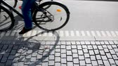 passeio : People cycling in Copenhagen, focus on bicycle shadows. Side view of a bicycle lane in the Danish capital, with many persons commuting by bike.