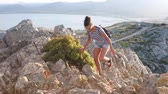 espanha : Beautiful woman on top of rocks in Majorca at sunset. Young woman enjoying summer day exploring the island of Majorca and relaxing at the top. Stock Footage