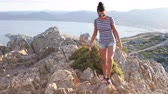 exploring : Beautiful woman on top of rocks in Majorca at sunset. Young woman enjoying summer day exploring the island of Majorca and relaxing at the top. Stock Footage
