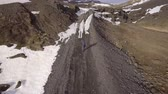 volcan : Man walking on a gravel road in Iceland. Aerial view with drone of a man exploring the Icelandic frozen countryside. Adventure and travel concepts