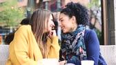Lesbian couple at a cafe. Two young women are having a coffee together, talking, cuddling and give each other a kiss. Candid situation with real people. Homosexuality and lifestyle concepts.