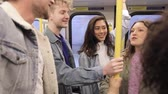 Group of young friends travelling together by tube in London - Mixed race group, two men and three women, talking and having fun together in the train - Friendship and transport concepts