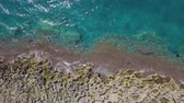 Aerial top view of coastline with waves breaking on the rocks. Rocky seaside in south of Italy, with emerald water in the sea. Travel and nature concepts