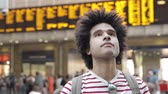cabelos cacheados : Mixed race man at train station portrait  - Afro caribbean man looking around while waiting for the train - Travel and lifestyle concepts Vídeos