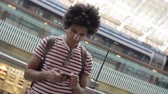 cabelos cacheados : Mixed race man typing on his phone, rotating video - Spinning video with gimbal of a man at train station using a smartphone while waiting to leave