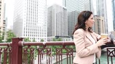 同僚 : Business people meeting and talking in Chicago. Man and woman, wearing smart casual clothes, looking each other and smiling. Downtown skyscrapers on background 動画素材