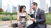 Business people having lunch at park in Chicago. Man and woman, wearing smart casual clothes, eating pasta and salad on lunch break. Downtown skyscrapers on background