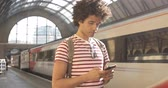Man at train station checking timetables on mobile phone - Mixed race man using his smartphone while waiting for the train - Travel and lifestyle concepts Wideo