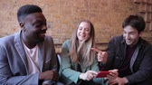 Happy friends having fun at bar and looking at smartphone - Multiracial group enjoying time at pub restaurant drinking together - Funny people smiling and laughing, happy lifestyle Wideo