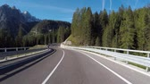 Driving on Italian alps with beautiful mountains on background. Empty road in Trentino, Italy, with green trees and meadows. Travel and transportation concepts Wideo