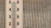 Increasing temperature on wooden thermometer with red scale