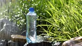 Bottle of water in garden on stones near fountain with water drops Стоковые видеозаписи