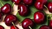 Ripe sweet cherry rotating top view on wooden background Stok Video