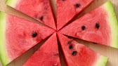 delicioso : Slices of watermelon rotating top view on wooden background Vídeos