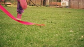 ribbon : Little girl playing with ribbon in the park and doing cartwheel