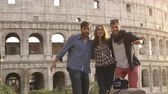 picture : Three young friends tourists jumping in front of colosseum in rome at sunset taking selfie pictures photos with dslr camera timer happy beautiful girl long hair slow motion Stock Footage
