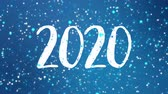 cartão de natal : Sparkly Happy New Year 2020 greeting card video animation with falling snowflakes and colorful glitter particles flickering on blue background. Vídeos