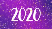фуксия : Sparkly Happy New Year 2020 greeting card video animation with handwritten numbers and colorful glitter particles flickering on purple background.