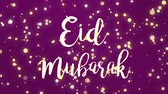 al adha : Glowing dark purple pink Eid Mubarak greeting card video animation with handwritten text and falling sparkly yellow particles.