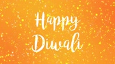 wenskaart : Sparkly Happy Diwali greeting card video animation with handwritten text and colorful glitter particles flickering on yellow orange background. Stockvideo