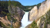 parkosított : Lower Falls of the Yellowstone River illuminated in bright sunlight at Yellowstone National Park of Wyoming Stock mozgókép