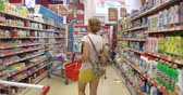 grocer : Girl chooses goods and meal in the supermarket. Shopping in the store. Young female is carefully analyzing products in a market. Stock Footage