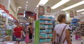 commerce : Girl chooses goods and meal in the supermarket. Shopping in the store. Young female is carefully analyzing products in a market. Stock Footage