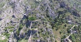 harabeler : Flight above the ruins of the ancient fortress in Old Kotor. Aerial view of Old Kotor, its mountains and ruins of the fortress with Montenegrin national flag on the top of the mountain Stok Video
