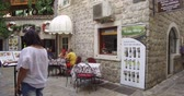 consumir : A small cozy open-air cafe on the old street in the center of a town. Tourists watch the menu and choose what to order, others sit at a table and talk