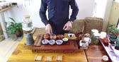 konvice : Chinese tea tasting in the tea shop. Tea seller, dressed in european, brews Chinese tea for tasting. Chinese tea set, traditional chinease teapot and cups on bamboo mats