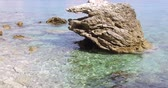 puro : Smooth green and turquoise water ripples on the sea water. Clear water reflects sunlight. Stone is seen in the water