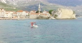 Budva, Montenegro, April 15, 2019: Beautiful seascape on the Adriatic Coast on a sunny spring day. The old stone fortress of Budva on the seashore. Tourists go on a motorboat