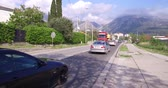 automobilista : Bar, Montenegro, April, 17, 2016: Road traffic in Montenegro. Cars, trucks and motorcycles. Sky is blue, its a sunny day. Mountains on the background