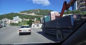 Budva, Montenegro, April 18, 2019: Frontal view through a sunny sunny day. The car overtakes a large truck