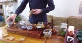 konvice : Chinese tea tasting in the tea shop. The seller, dressed in European, brews Chinese tea for tasting. Chinese tea set, traditional Chinese teapot and cups on bamboo mats