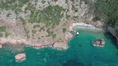 guarda chuva : Drone flies above the coastline of the Adriatic sea, southern Montenegro, in a sunny summer day. Water in the sea is turquoise, clean and clear Vídeos