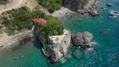Drone is flying around a steep rocky sea shore, onto which turquoise waves of the Adriatic Sea roll. Houses are visible on the peninsula covered with pine trees and coniferous trees