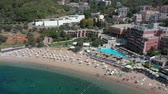 Low flying aerial drone footage of vacationing tourists, waves and sunshine on the beautiful shores and sandy beach of landmark Budva. Sea waves roll in the seashore