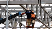 kaynakçı : a welder working at height without insurance in a cradle lift in the construction of large shopping complex metal structures and concrete piles.