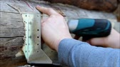 Assembling a wooden frame and building a house. Russia. The worker screw the screws into the pre-drilled holes with a screwdriver. Stok Video