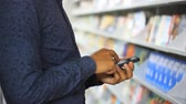 handheld : man uses his smartphone at the book store