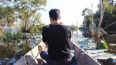 sideview : birdwatcher working on the boat trip in the bird swamps Stock Footage