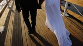 confident : Beautiful visuals on a young couple who had just left the church to get married, and they go on the pier, on the left we see the open water, the right large yachts or boats, they go and holding hands, in the hands of the brides bouquet of delicate light